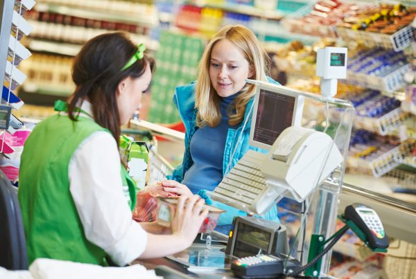 Woman buying at store using mobile financial services, financial transactions